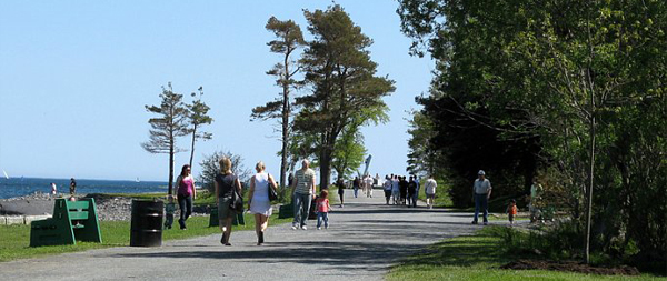 People strolling down a park path by the ocean.